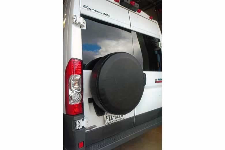 A custom white Sportsmobile conversion van with an upgraded exterior tire mount attached to the rear door.