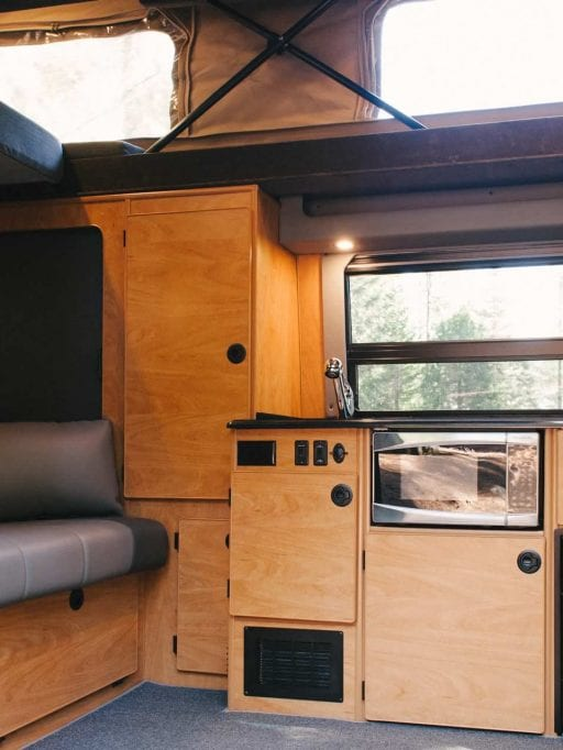 Interior view of Sportsmobile camper van converison with the penthouse top open.
