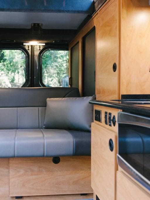 Interior view of Sportsmobile camper van conversion with sofas in the rear.