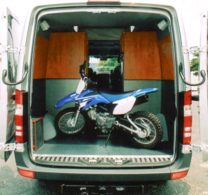 Rear view of a motorcycle parked in the cargo area of a white Sportsmobile conversions van.