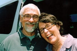 Jim and Karen Duncan smiling and laughing next to their white Sportsmobile custom camper van.