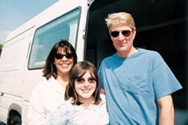 The Knott family stands next to their white Sportsmobile custom camper conversion van.