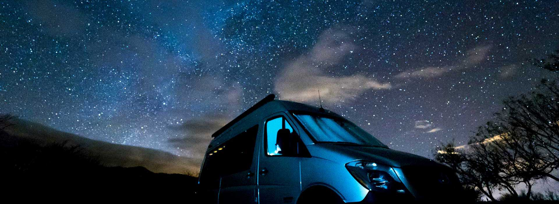 Sportsmobile Sprinter van conversion camping under the night sky.