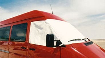 A red custom Sportsmobile van conversion with windshield screens installed.