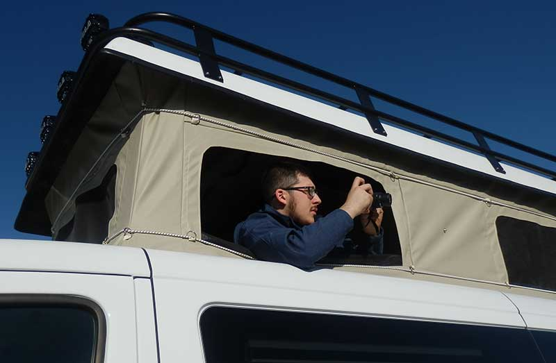A Sportsmobile owner taking photos out of one of the windows of his custom penthouse pop top conversion.