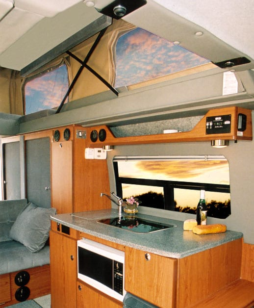 An interior view of a custom Sportsmobile Sprinter camper conversion van with the penthouse pop top exanded.