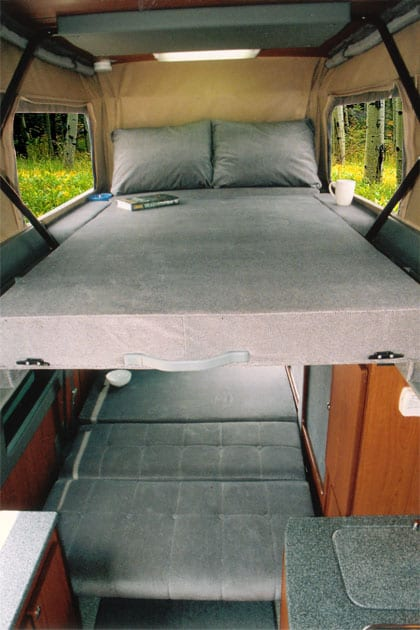 An interior view of a custom Sportsmobile camper van conversion with an upstairs bed option.