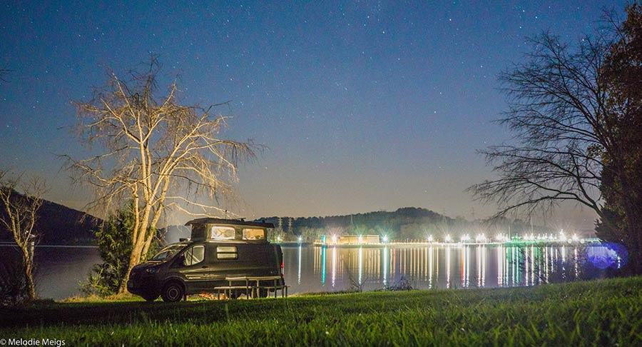 A night photo of a custom Sportsmobile camper van conversion with the lights on inside, next to a lake and a city full of lights in the background.