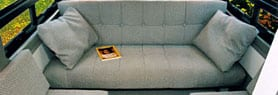 Interior view of sofa that turns into a bed in a Sportsmobile van conversion.