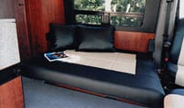 Interior view of a Gaucho with pillows in a Sportsmobile van conversion.