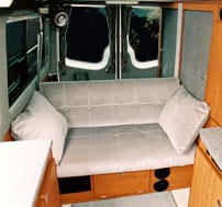 Interior view of sofa that seats three in a Sportsmobile van conversion.