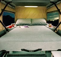 Interior view of an expanded penthouse top bed in a Sportsmobile van conversion.