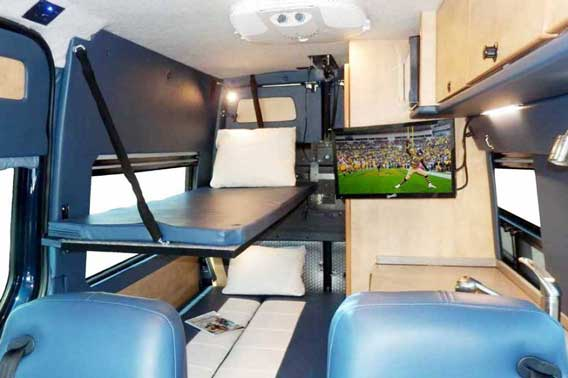 Van conversion with built in TV, cabinets, and double beds.