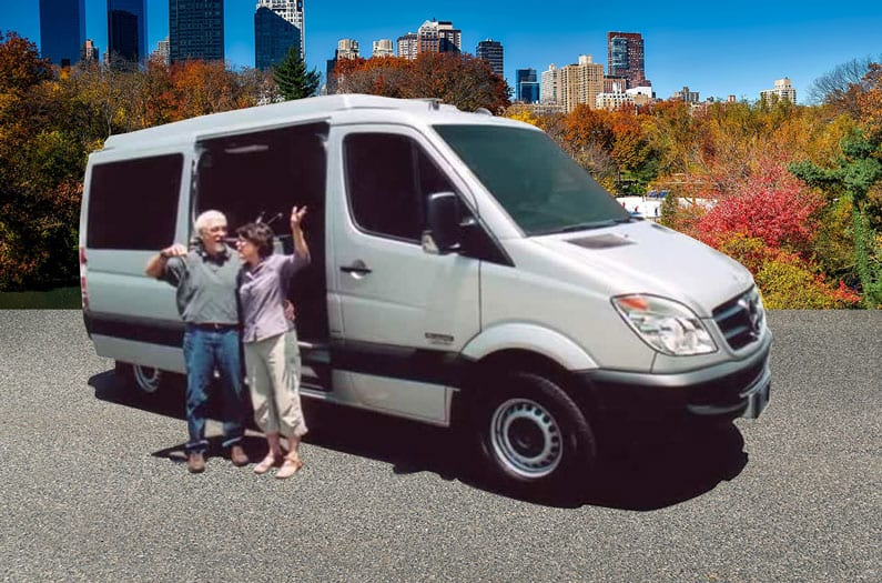 Happy Sportsmobile Sprinter owners stand next to their white conversion van.