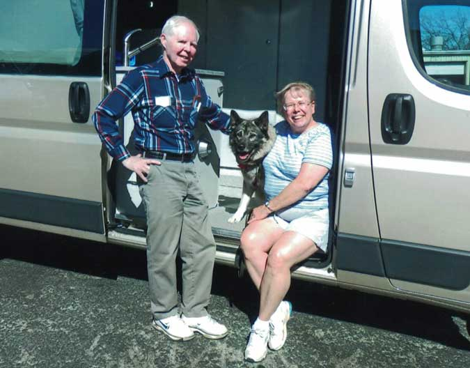 The Whitmans and their dog rest in the doorway of their silver Sportsmobile ProMaster camper conversion.