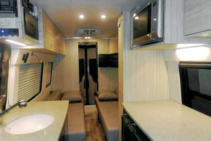 Interior view of a custom Sportsmobile van conversion featuring a kitchen and sleeping area.