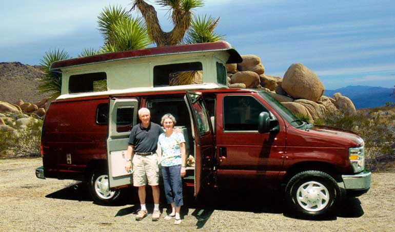 Proud Sportsmobile owners stand next to their maroon Sportsmobile camper van conversion.