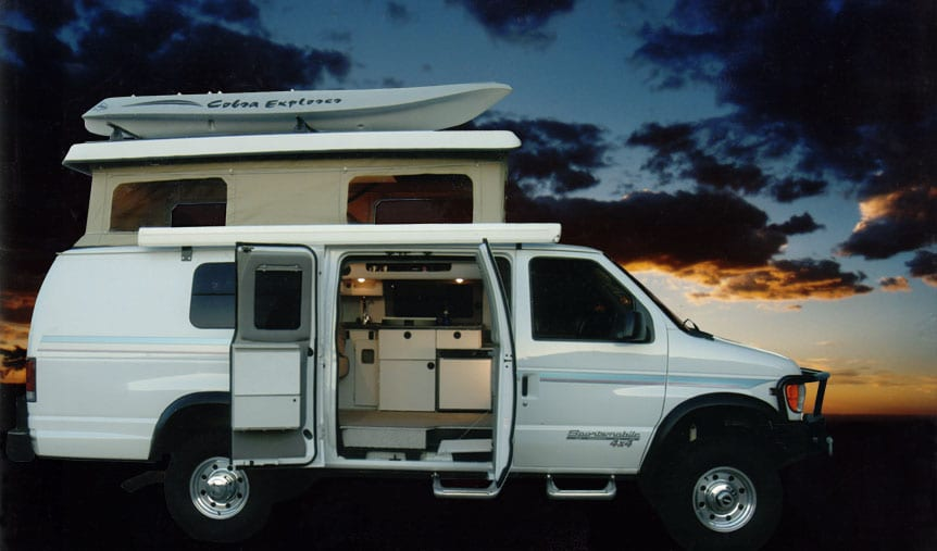 A white custom Sportsmobile 4x4 camper conversion with the penthouse top up.