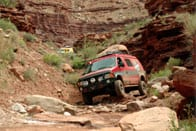 A red Sportsmobile conversion traveling over rocks.