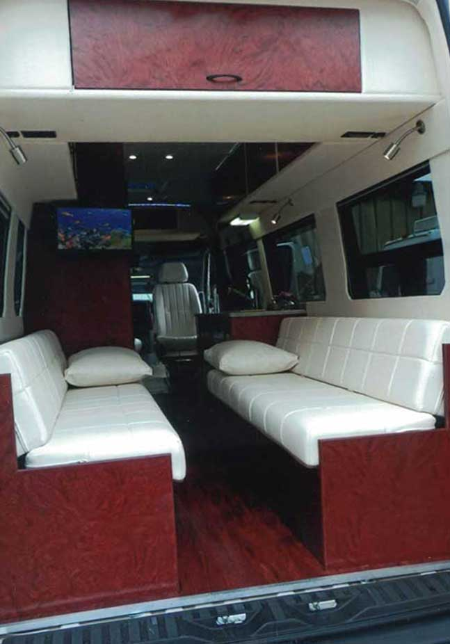 Inteior view of upgraded dinette that seats six in a custom Sportsmobile van conversion.
