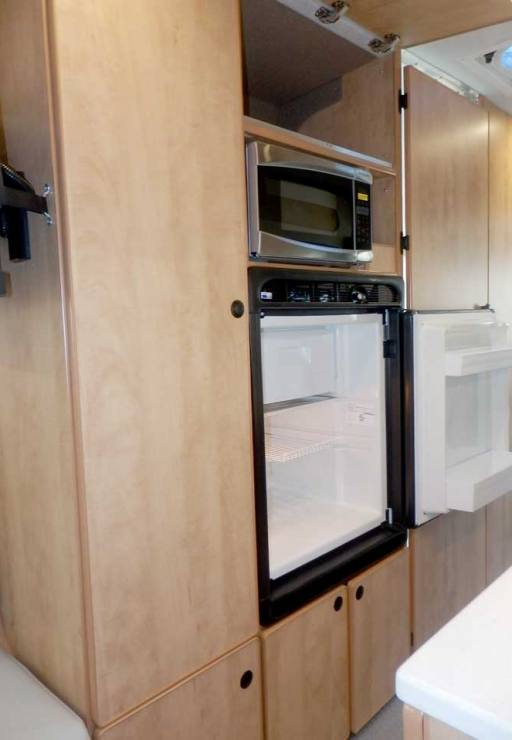 Ford Transit camper conversion featuring a microwave and refrigerator in the galley.