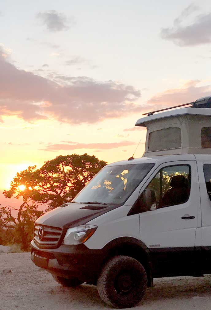 White Sportsmobile camper van conversion at sunset.