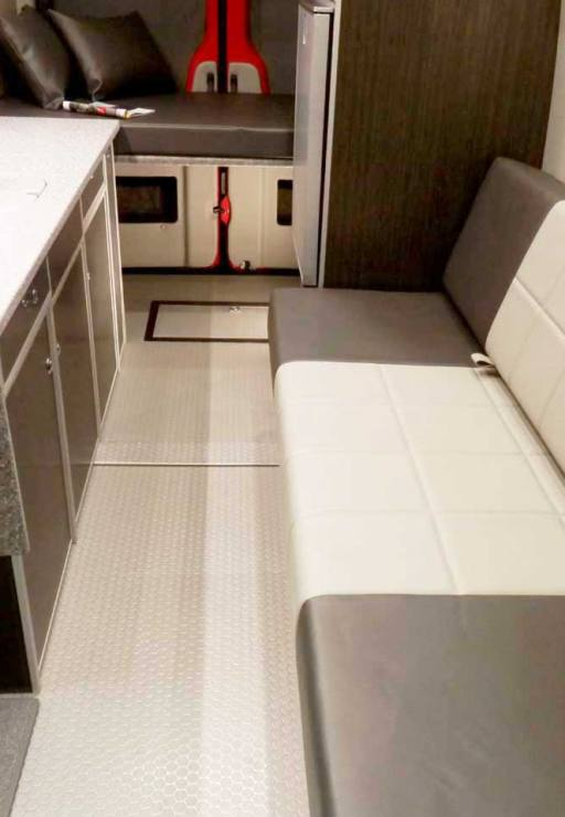 Interior view of a custom Sportsmobile Sprinter 4x4 van conversion with gaucho seats with seat belts and cushions.