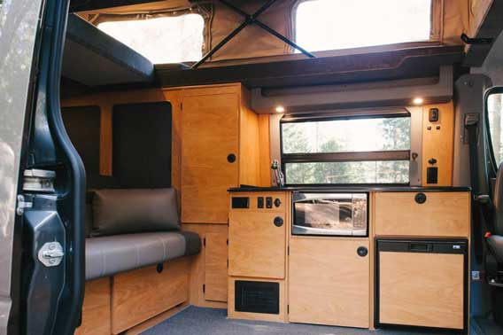Custom wood cabinets and trim in this Sprinter van conversion.