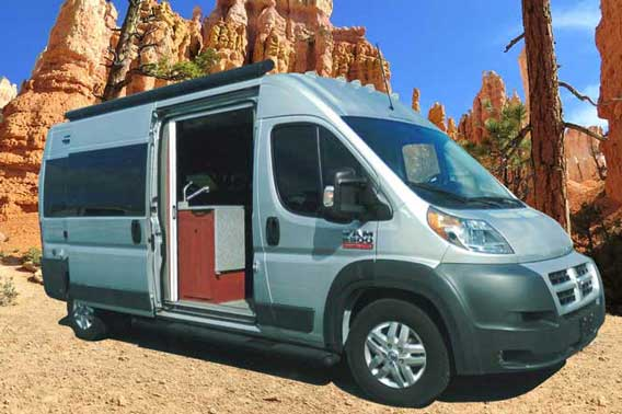 Grey Dodge ProMaster van conversion traveling through the desert.