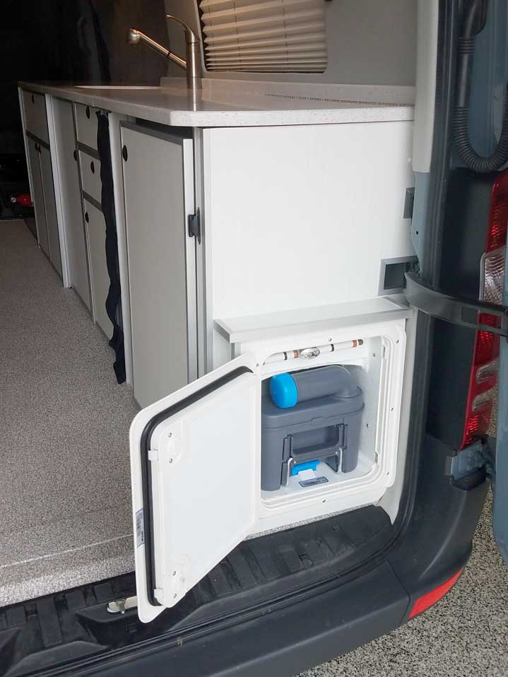 Interior view of compartment doors open exposing the toilet in a Sportsmobile conversion van.