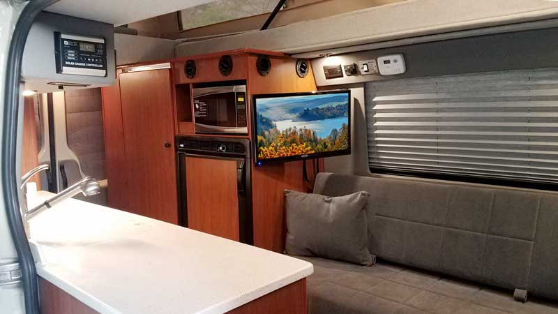 Interior view of a custom Sportsmobile Sprinter van conversion with a TV.
