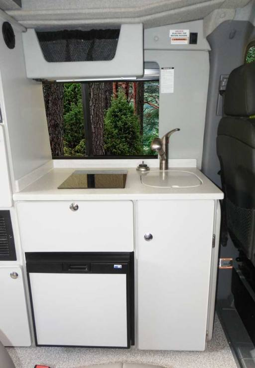 Custom Mercedes-Benz conversion van's galley includes cabinets and appliances.