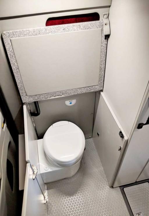 Door and extension open exposing interior toilet.