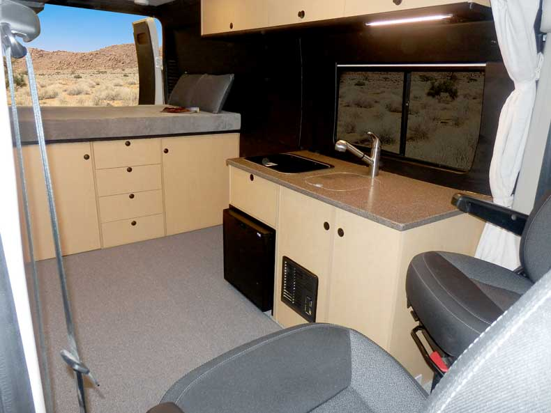 Custom Sportsmobile Promaster conversion van featuring a platform bed.