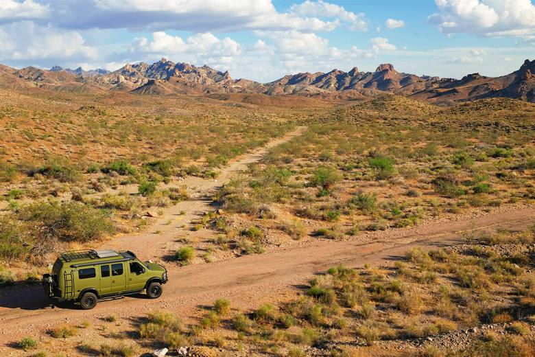 Off road green Sportsmobile Classic 4x4 Ford trek in the desert.
