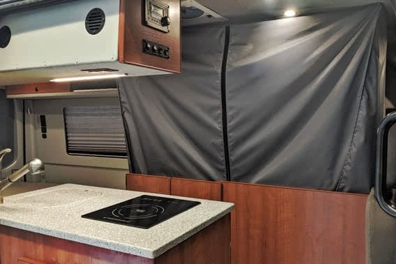 Galley and bath compartment areas made of custom wood cabinetry.